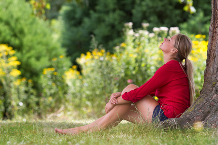 eyes closing: wellbeing & tree concept - serene young blond woman sitting under a tree,closing eyes enjoying freshness,natural summer daylight