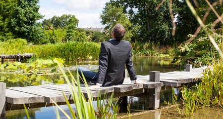corporate green break - relaxed middle age male professional sitting on a wooden bridge in the middle of an asian-like green pond for company wellbeing,back view with park foreground