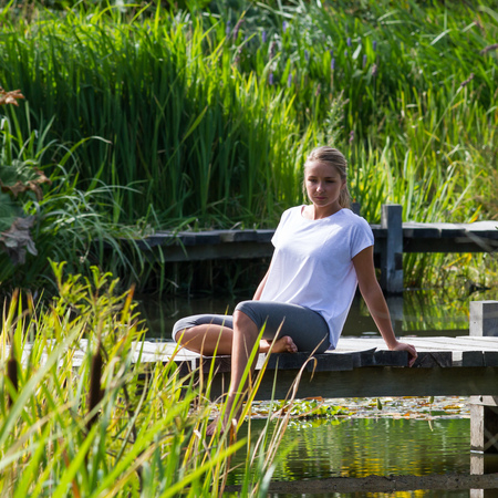 bare feet: relaxation outside - daydreaming young woman enjoying putting her bare feet in water,sitting on a wooden bridge, green park environment, summer daylight