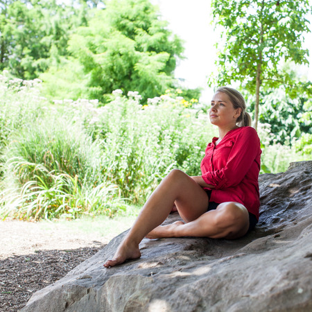suntanned: reflection & tree concept - beautiful young blond suntanned woman resting on a rock in the shade for relaxation,natural summer daylight Stock Photo