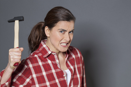 enraged: female DIY concept - enraged brunette woman holding hammer with violence,losing temper or frustrated at working manually