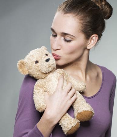 sexy young girl: сексуальная блондинка девушка целуя ее плюшевого мишку с нежностью для детей воспоминания Фото со стока