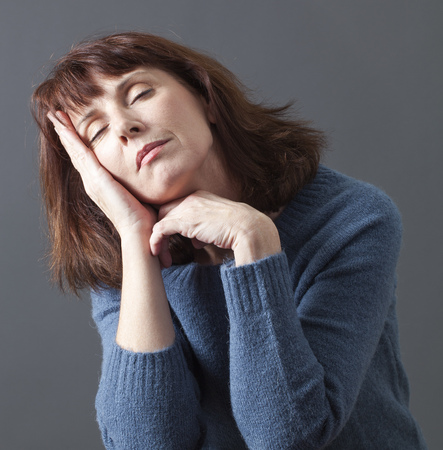 eyes closing: attractive 50s woman closing her eyes,seeking for relaxation with face leaning on hands to sleep or nap for menopause break Stock Photo