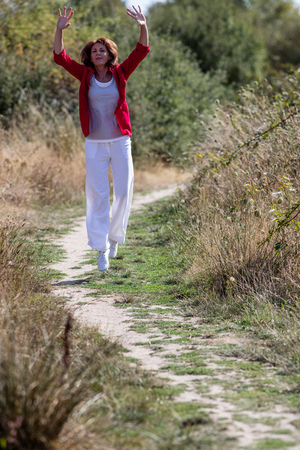 vitality: vitality outdoors concept - healthy mature woman jumping in walking in path for fun and energy,natural summer daylight