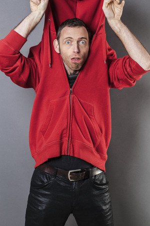 silliness: surprise and disappointment concept - portrait of a funny 40s man acting like an idiot playing with his hoodie up his head for silliness,studio shot