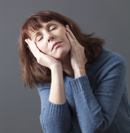 wellness sleepy: attractive mature woman closing her eyes,seeking for relaxation with face leaning on hands to sleep or nap for menopause break Stock Photo