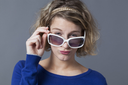 20s: adorable 20s girl looking over her girly sunglasses Stock Photo