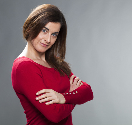 30s: satisfaction and smile concept - satisfied 30s businesswoman with arms crossed,looking on the side expressing happiness and wellbeing Stock Photo
