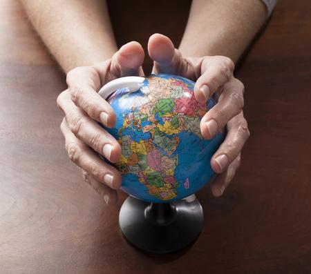 madre tierra: manos de la mujer que sostienen el globo para el cuidado de medio ambiente y preciosa madre tierra Foto de archivo
