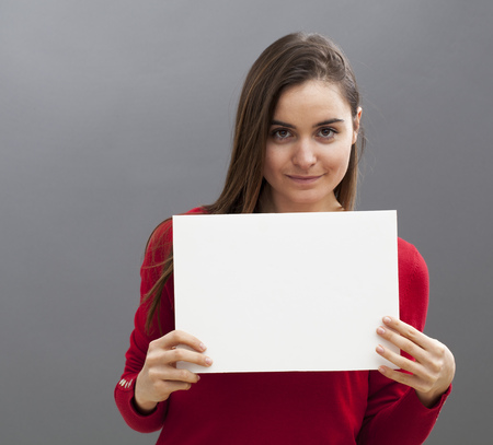 woman chest: seductive young woman wearing red holding a copy space communication board in front of her