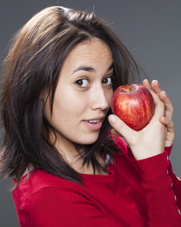 lady in red: smiling cute young brunette with red apple in hands