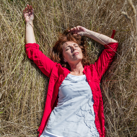 aging woman: sun warmth wellbeing - gorgeous aging woman enjoying sunbathing,lying alone in a summer grass meadow,natural daylight,overhead view,from above Stock Photo