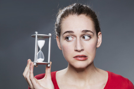 nervous beautiful young woman holding egg timer for concept of time management