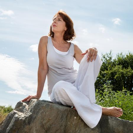 piedras zen: alto zen - mujer pensando 50s sentado en una piedra para la sesi�n de yoga al aire libre vestidos de blanco que buscan tranquilidad y bienestar en un parque, luz de d�a de verano Foto de archivo