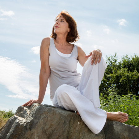 senior zen - thinking 50s woman sitting on a stone for outdoors yoga session wearing white seeking serenity and wellbeing in a park,summer daylight Stock Photo