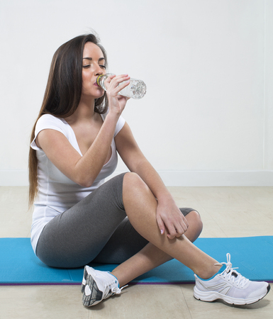 pilates studio: thirsty young fitness woman sitting on an exercise mat with gym clothes drinking water