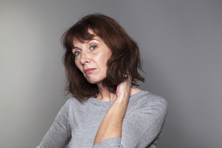 disillusioned: disillusioned mature woman with brown hair and grey sweater thinking,looking bored and concerned