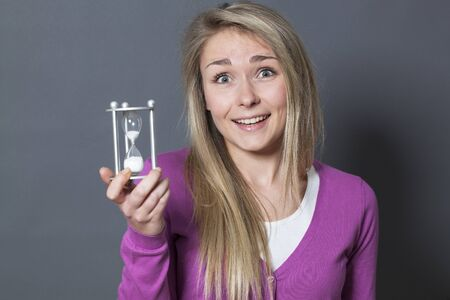thrilled young blond woman holding egg timer for concept of time management