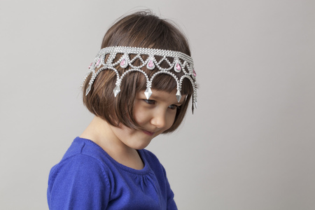 bebes niñas: niña pensando con la corona en la cabeza en el perfil de la sonrisa