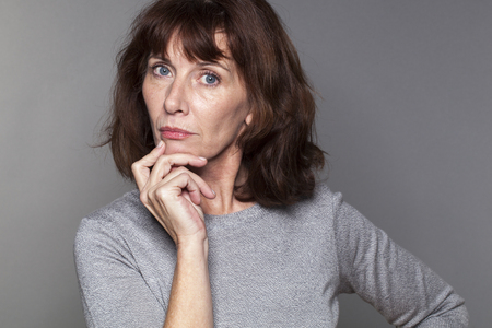 focused mature woman with brown hair and grey sweater thinking,looking sad and concerned