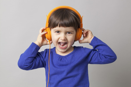 rhythms: thrilled young child enjoying rhythms in listening to music on headphones