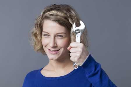 manual work: female DIY concept - successful young blond woman holding wrench or spanner with confidence and fun,enjoying manual work Stock Photo