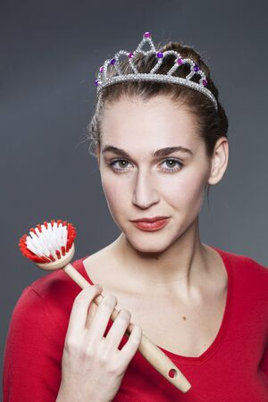 fussy: smiling young gorgeous woman wearing princess tiara with dish brush in hand for housekeeping queen or cleaning house master