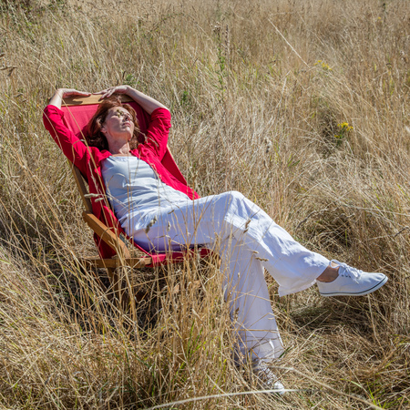 warmth: sun warmth wellbeing - relaxed mature woman enjoying sunbathing on deckchair,resting alone in long dry grass field,natural daylight