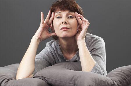 hermosa mujer madura levantando sus ojos naturalmente se relaja en cojines grises por concepto de cuidado de la piel contra el envejecimiento Foto de archivo