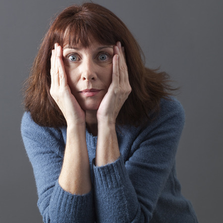 surprise and disappointment concept - portrait of a mature brunette woman expressing confusion putting both hands on cheeks for disillusion,studio shot