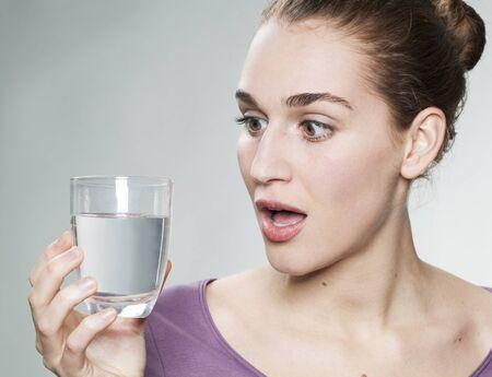 grifo agua: sorprendido mujer hermosa joven con el vidrio de color p�rpura camisa de retenci�n de agua del grifo pura
