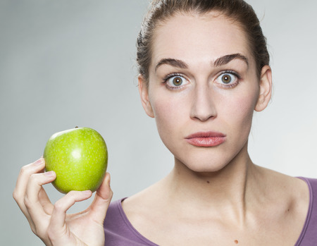 questionable: surprised beautiful young woman holding a perfect looking green apple for questionable healthy diet