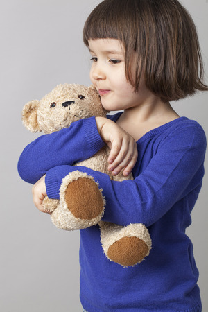quiet baby: happy preschool girl hugging her teddy bear with care and tenderness Stock Photo