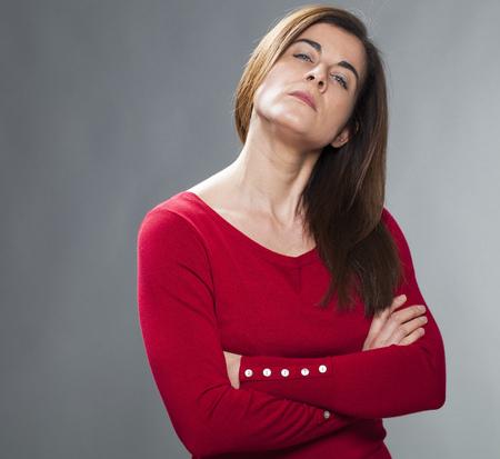 arrogancia: infeliz joven con el pelo marr�n y su�ter rojo con los brazos cruzados, mirando hacia arriba con la actitud y arrogancia
