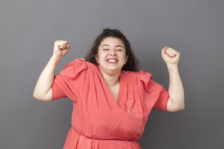 overweight girl: success concept - tensed young overweight girl wearing vintage clothes smiling expressing her achievement and happiness Stock Photo