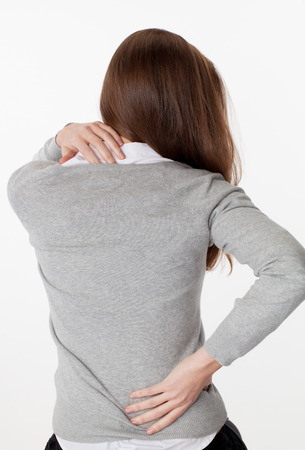 backache concept - young woman massaging her back from up and down for tension relief and posture relaxation,back view on white background Foto de archivo