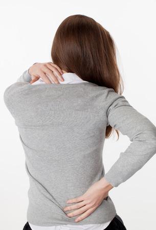 rugpijn concept - jonge vrouw masseert haar rug uit op en neer voor de trekontlasting en houding ontspanning, terug te bekijken op een witte achtergrond Stockfoto