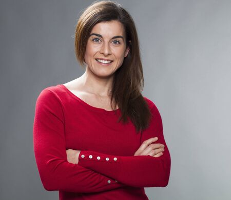30s: happy 30s woman with arms folded, wearing red sweater, expressing wellbeing and happiness