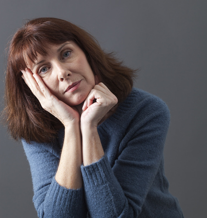 woman middle age: nostalgic beautiful 50s woman with winter sweater with head leaning on hand,looking depressed with seasonal affective disorder syndrome,studio shot Stock Photo