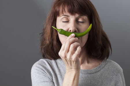 chili: serene beautiful mature woman holding green pepper as moustache for sexy concept