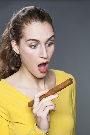 big girl: surprised young female playing with the symbol of successful industry and concept of business woman Stock Photo