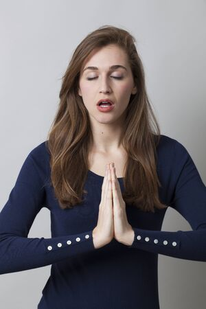 closing: meditation concept - zen smiling young woman wearing a smart navy blue sweater holding hands together,closing eyes for relaxation