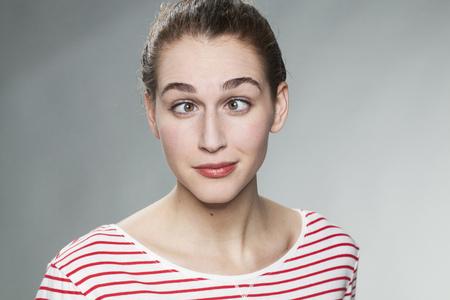 concepto del humor - retrato de una mujer joven bizco que llevaba un jersey de rayas que se divierte en la práctica de una cara divertida con los ojos