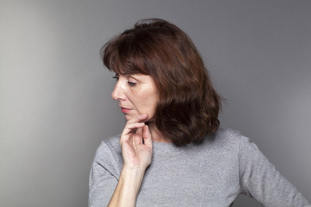 profile view: depressed mature woman with brown hair and grey sweater thinking,looking concerned and thoughtful, profile view