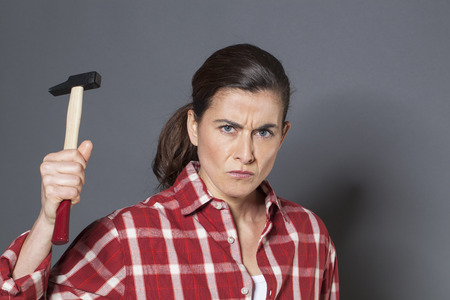threatening: female DIY concept - threatening young brunette woman holding hammer with violence,losing temper or angry at having to work manually