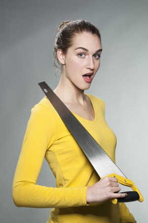 prove: female DIY concept - surprised beautiful young woman holding saw to prove her home improvement expertise