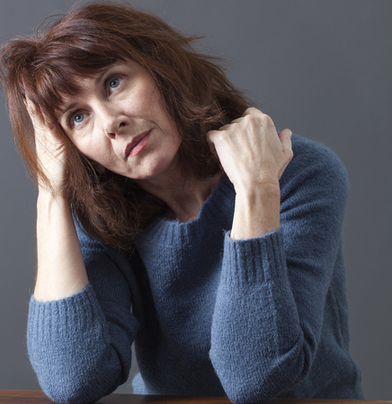 uncombed: portrait of mature uncombed woman with brown hair and blue winter sweater thinking,head leaning on hand,looking imaginative Stock Photo