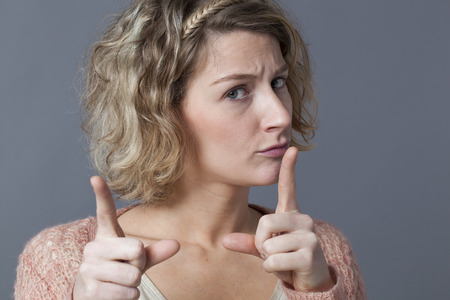 behaving: threatening 20s blonde girl showing her index finger for signal of keeping away, forbidding or behaving with unhappiness Stock Photo