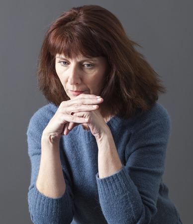 trieste vrouw 50's alleen met kin rustend op de handen voor reflectie, verdriet of vermoeidheid als gevolg van de menopauze