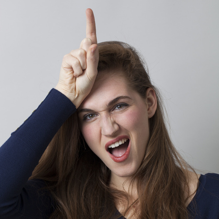 irrespeto: mujer joven divertido haciendo la señal L en la frente para el mensaje perdedor, gesto de mano fría de la cultura juvenil